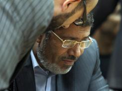 Muslim Brotherhood presidential candidate Mohammed Morsi confers with an aide during a meeting in Cairo on June 3.