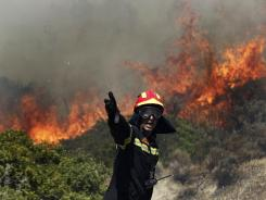 A firefighter gestures instructions to his colleagues as a fire rages in Palea Fokaia, south of Athens, on Saturday.