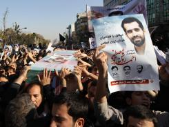 Mourners carry the coffin of Iranian nuclear scientist Mostafa Ahmadi-Roshan in Tehran on Jan. 13, one day after he was killed when two men on a motorbike slapped a magnetic bomb on his car.