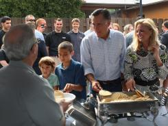 Mitt Romney and wife Ann, at right, serve pancakes Sunday in Brunswick, Ohio.