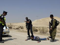 Israeli police officers and a soldier detain an Arab-Israeli on Monday after he tried to pass a roadblock in the Israeli Negev desert. A manhunt continued for gunmen who infiltrated from Egypt.