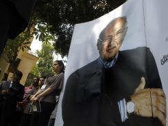 Campaign officials of Egyptian presidential candidate Ahmed Shafiq stand next to his poster during a press conference in Cairo on Monday.