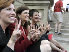 Rep. Barb Byrum, left, Rep. Lisa Brown, playwright Eve Ensler and Sen. Rebecca Warren pose for a picture during a performance of The Vagina Monologues on the Michigan Statehouse steps on Monday.