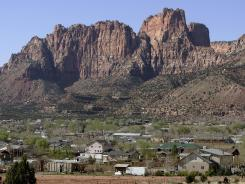 Colorado City, Ariz., in the foreground, and Hildale, Utah, are being sued by the Justice Department.