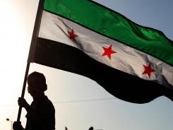 A boy waves the Syrian revolutionary flag during Thursday's protest in front of Syria's embassy in Amman, Jordan.