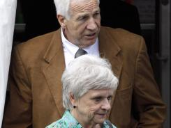Former Penn State University assistant football coach Jerry Sandusky, rear, and his wife Dottie leave the Centre County Courthouse in Bellefonte, Pa.