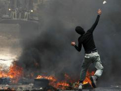A Palestinian protester throws a stone at Israeli soldiers during a demonstration Friday. Israel says an airstrike killed a man before he could fire a missile from Gaza.