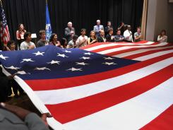 U.S. citizenship candidates roll out a replica of a flag from the War of 1812 era June 14 at the Maryland Historical Society in Baltimore.