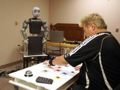 "A new kind of therapist: Steve Dimon, a stroke patient at Rancho Los Amigos Rehabilitation Center in California, does exercises with the help of Bandit, an assistive robot. ""It was like a diversion from the tediousness of rehab,"" Dimon says."