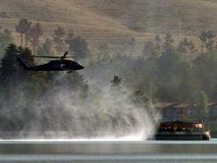 A UH-60 Black Hawk helicopter flies near the Spozhmai Hotel in Qargha lake in the outskirts of Kabul on Friday.