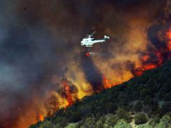 Emergency responders work on a wildfire Friday that is threatening homes in Saratoga Springs, Utah.