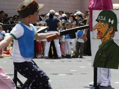 A student points a toy gun at a painting of a U.S. soldier during a game June 1 on the grounds of Kyongsang Kindergarten in Pyongyang, North Korea, as the country marked International Children's Day.