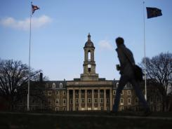 A student walks in front of the Old Main building on the Penn State campus on Nov. 11, 2011, in State College, Pa.