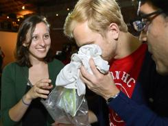 Konstantin Bakhurin, center, smells a shirt as Martina Desalvo, left, and Neelroop Parikfhak look on during a pheromone party in Los Angeles.