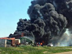 Smoke rises from two cargo trains that collided two miles east of Goodwell, Okla.