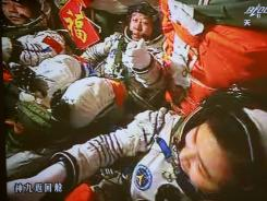 In this image made off the monitor screen at the Beijing Aerospace Flight Control Center, China's astronauts Jing Haipeng, center, Liu Wang, left, and Liu Yang sit inside the Shenzhou-9 manned spacecraft on June 18.