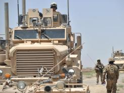 American might: Marines patrol a village near Helmand province, Afghanistan, this weekend.