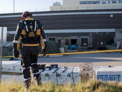 A rescue worker walks Monday toward the emergency staging post at the Algo Centre Mall in Elliot Lake, Ontario.