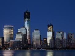 Construction cranes perch on top of One World Trade Center, left, and Four World Trade Center in New York.