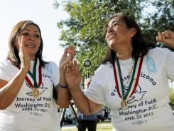 Maria Durand, left, and Rosa Maria Soto, both from Arizona, cheer as they react to the Supreme Court decision regarding Arizona's controversial immigration law at the Arizona Capitol in Phoenix.