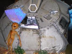 This photo taken in December 2006 at the Area 51 exhibit at the Alien Zone in Roswell, N.M., shows an alien standing outside a crashed spaceship. More than one-third of Americans believe aliens exist, according to a National Geographic survey.