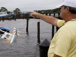 Mark Mitchell surveys damage to boats at the Rock Landing Marina in Panacea, Fla., on Tuesday.