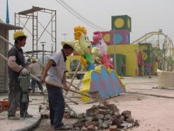 Workers make final preparations at Victory Kingdom, a U.S.-style theme park set to open this summer in the north China city of Tianjin.