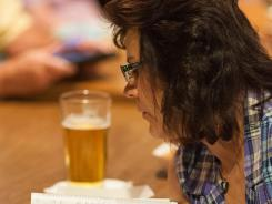 Linda Myatt leans over to read a Bible passage during a meeting at Uncle Charlie's Bar in Cheyenne, Wyo.