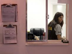 DEA special agent Jeannette Moran collects evidence Wednesday from a clinic in Miami.