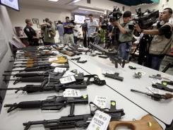 Confiscated: Guns displayed in Santa Ana, Calif., from an investigation into gangs affiliated with the Mexican mafia.