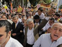 Andres Manuel Lopez Obrador, center, presidential candidate of the Democratic Revolution Party, waves to supporters as he walks toward the main Zocalo plaza in Mexico City on Wednesday.