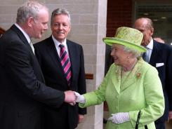 Britain's Queen Elizabeth II shakes hands with former IRA commander Martin McGuinness on Wednesday in Belfast, Northern Ireland.