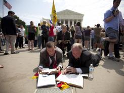 After the health care ruling, demonstrators pray outside the Supreme Court on Thursday.