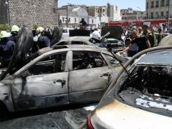 Burnt cars are seen at the site of a blast Thursday in Damascus, Syria.