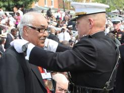 Lt. Gen. Robert P. Neller presents a congressional gold medal to a member of the Montford Point Marines during a ceremony held at the Marine Corps Barracks in Washington, D.C.