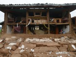 A damaged house is cleared after an earthquake on June 25, in Lijiang, China.
