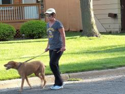 Getting physical: Denise Hrncir of Farmington, Minn., who often doesn't have time to exercise during the week, walks her dog as part of her weekend routine.