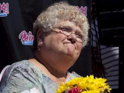 Bus monitor Karen Klein, of Greece, N.Y., holds flowers Thursday during an award ceremony in her honor at a radio station in Boston.