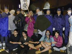 People sit in protest on a road near the entrance to the Ohi nuclear power plant in Fukui, Japan, on Sunday.