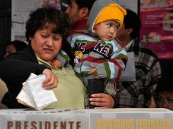 A woman with her child casts a vote in the presidential election Sunday in Atlacomulco, Mexico.