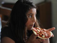 Michelle Berrios, 9, enjoys a do-it-yourself pizza as part of the summer food program at Greenbrier Learning Center in Arlington, Va.