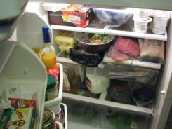 Families have to decide which items to remove from their refrigerators after losing power.