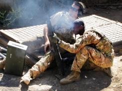 Sgt. Mat Hanson, left, and Spc. Ryan Jackson fire mortars at the nearby mountainside during a firefight at Combat Outpost Pirtle King in eastern Afghanistan.