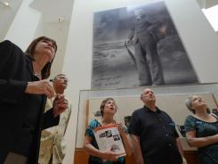 Barbara Johnson Ross, left, curator of collections at the Ohr-O'Keefe Museum of Art gives a tour to visitors beneath the towering photo of legendary potter George Ohr. Biloxi, Miss., seemed on the brink of collapse after Hurricane Katrina and the BP oil spill. Today, a glimmering Frank Gehry-designed art museum stands where storm debris once piled up.