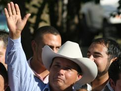 In this 2010 photo, horse owner Jose Trevino Morales acknowledges the crowd as he stands with the trophy at the All American Futurity horse race at Ruidoso Downs, N.M.