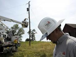Linemen from Gulf Power of Pensacola, Fla., work to replace downed power lines in Middleburg, Va., July 3.