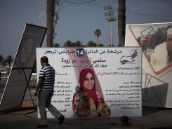 A Libyan man walks near National Assembly election campaign posters at Martyr's Square in Tripoli, Libya, on Thursday.