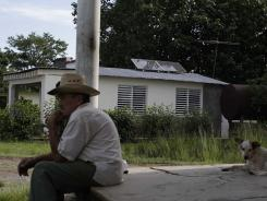 Marcos Portales sits on the edge of a porch backdropped by a solar-powered video room, in Pinar del Rio, Cuba, on June 18.