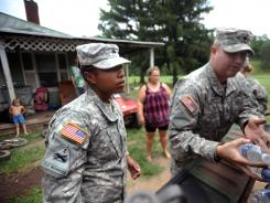 National Guard Sgt. Jessica Homeres, left, and Spc. Jeremy Lemaster, right, deliver food and water to the home of Dewan Dunbar, 40, center, on Thursday in Heaters, W.Va.