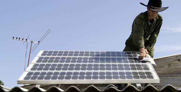 Yusmaikel Portales cleans the solar panel on the roof of his grandfather's home in Pinar del Rio, Cuba, on June 18.